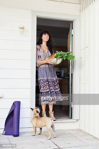 Young woman in doorway holding bowl of vegetables