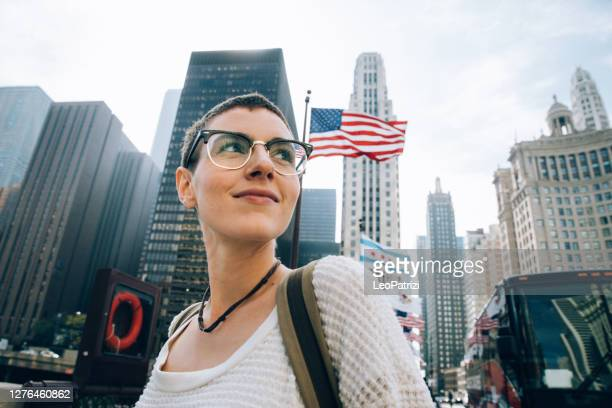 young woman in downtown with an us flag on the background - activist stock pictures, royalty-free photos & images