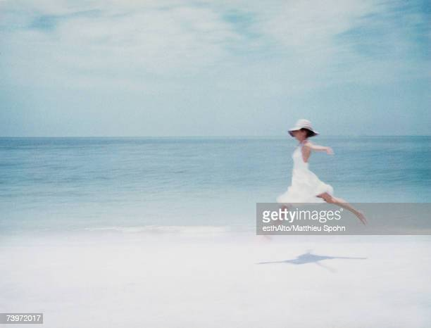 Young woman in dress leaping on beach, arms out, side view
