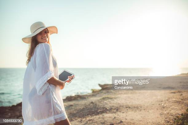 young woman in dress standing by blue sea - hot body girls stock photos and pictures