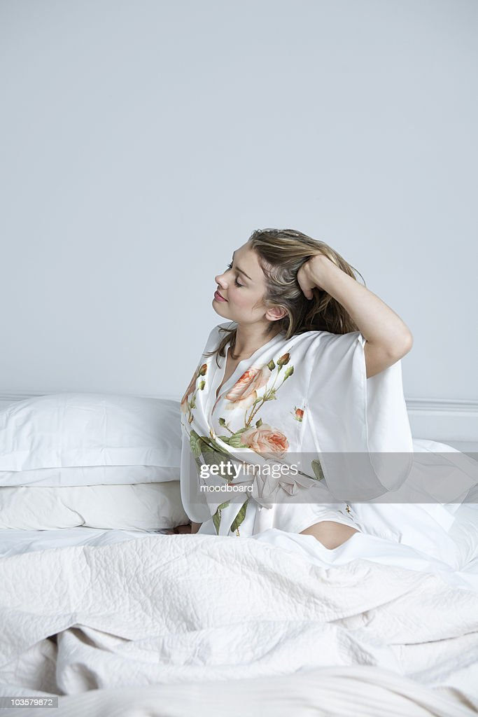 Young Woman In Dressing Gown Stretching In Bed Stock Photo | Getty ...