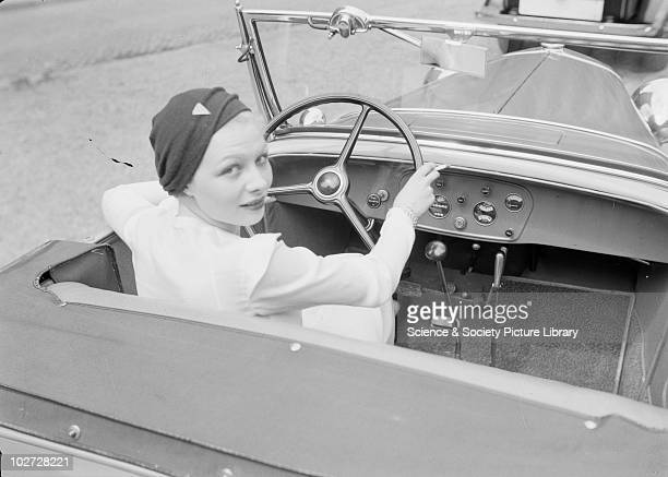 Young woman in driving seat turns to face rear of car Photograph taken by Zoltan Glass c1930 Photograph taken for advertisement series in the early...
