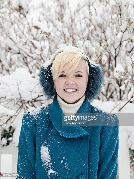 Young woman in earmuffs outdoors in winter