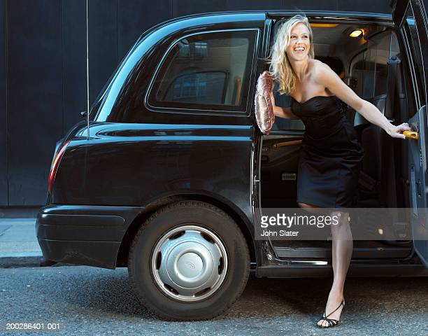 young woman in evening dress, exiting taxi, smiling - vestido preto - fotografias e filmes do acervo