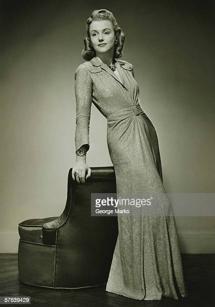 Young woman in evening dress leaning against chair, (B&W)