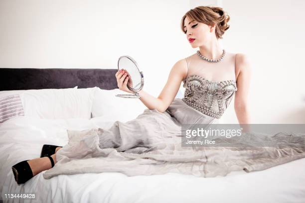 young woman in evening gown gazing at herself in mirror whilst reclining on bed - ijdel stockfoto's en -beelden