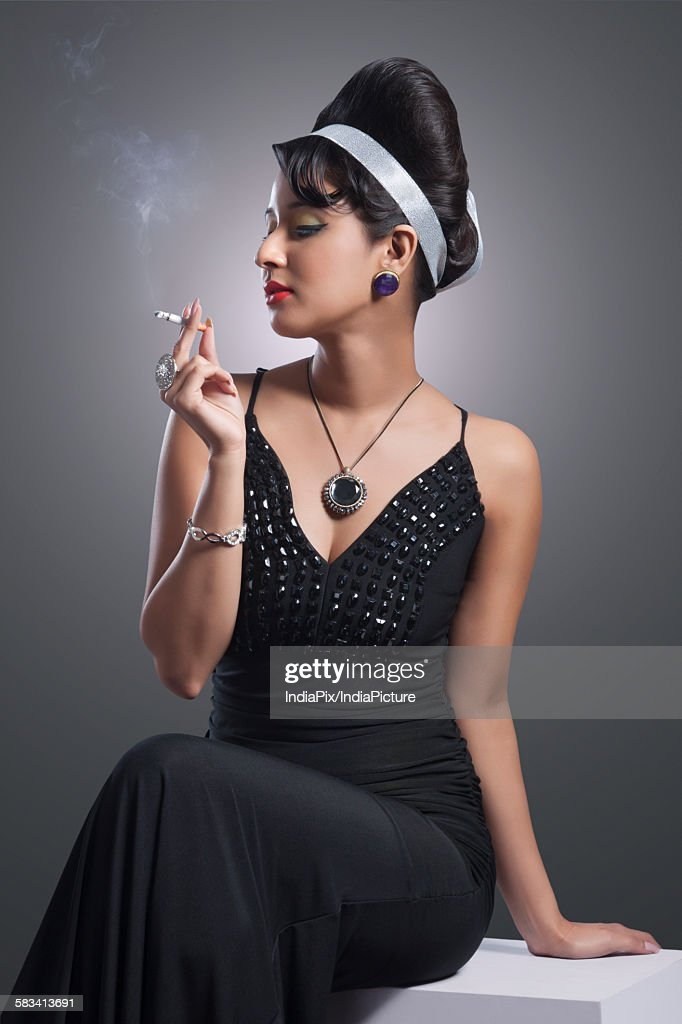 Young woman in evening gown smoking : Stock Photo