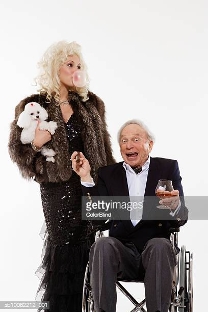 young woman in evening wear, blowing bubble gum next to old man in wheel chair - sugar daddy stock photos and pictures