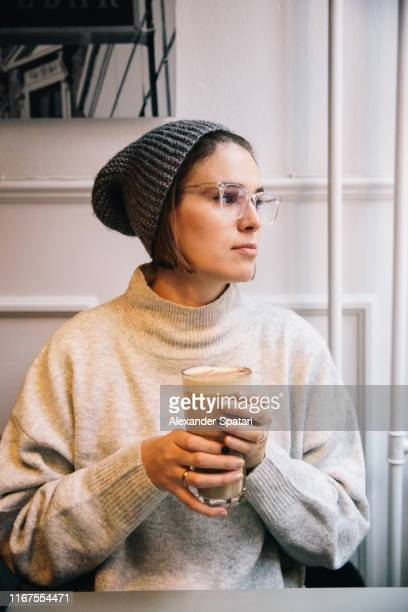 young woman in eyeglasses drinking coffee in a cafe - gray hat stock pictures, royalty-free photos & images