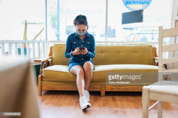 young woman in face mask with phone - mini dress stock pictures, royalty-free photos & images