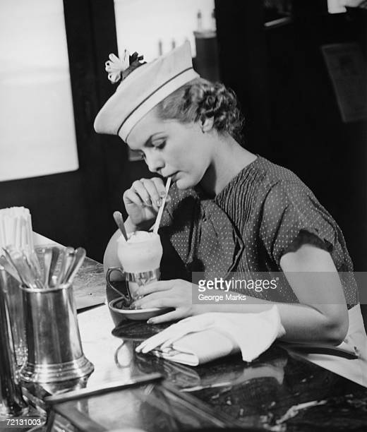 young woman in fancy hat drinking ice cream soda (b&w) - diner stock pictures, royalty-free photos & images