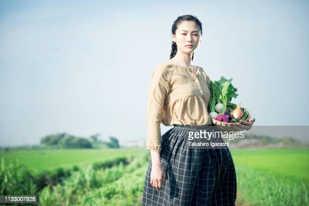 young woman in field holding basket of homegrown vegetables - 農園 ストックフォトと画像