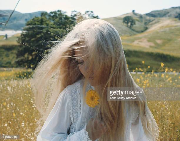 Young woman in field holding flower