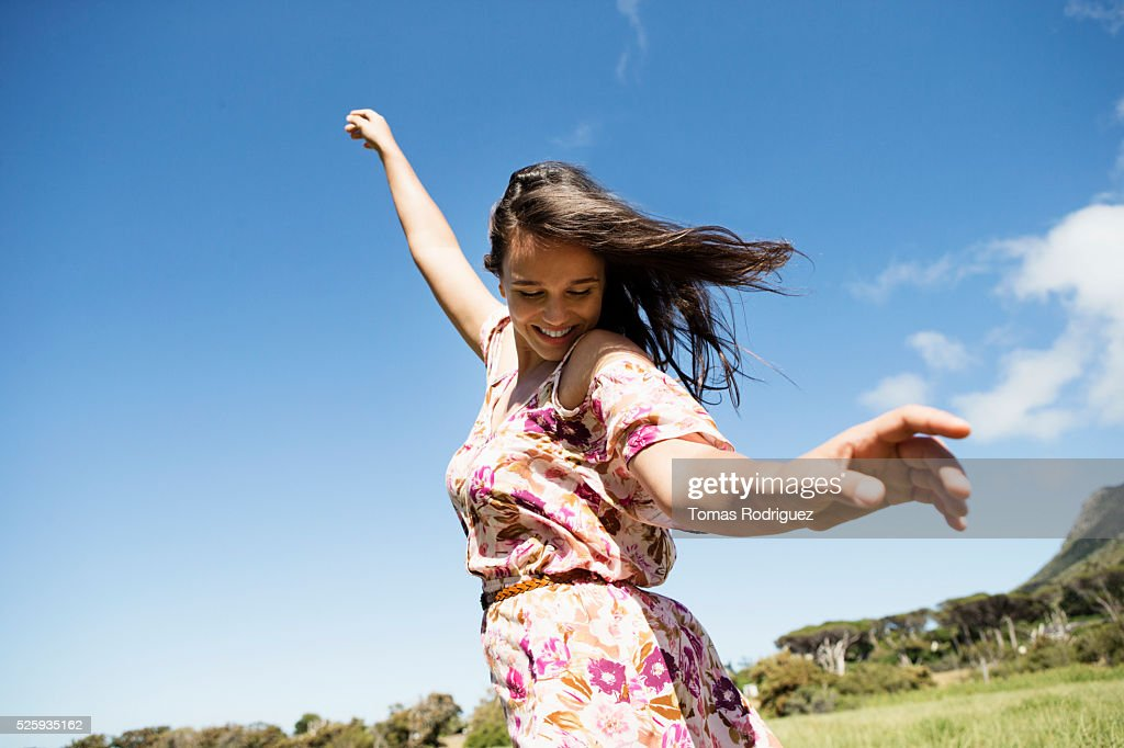 Young woman in field with arms raised : Stock-Foto