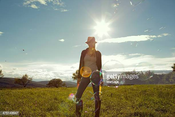 young woman in field with blown bubbles - 麦わら帽子 ストックフォトと画像