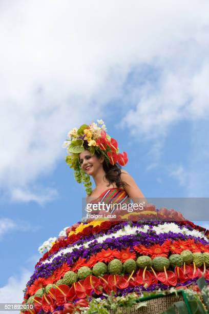 Young woman in floral costume on float during parade at annual Madeira Flower Festival, Funchal, Madeira, Portugal