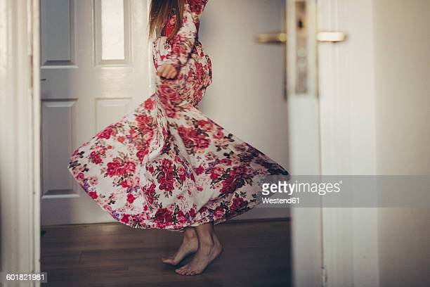 Young woman in floral dress moving on the floor