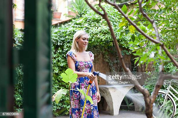 Young woman in floral dress watering plants