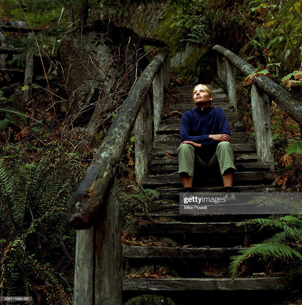 Young Woman In Forest Sitting On Wooden Staircase Looking
