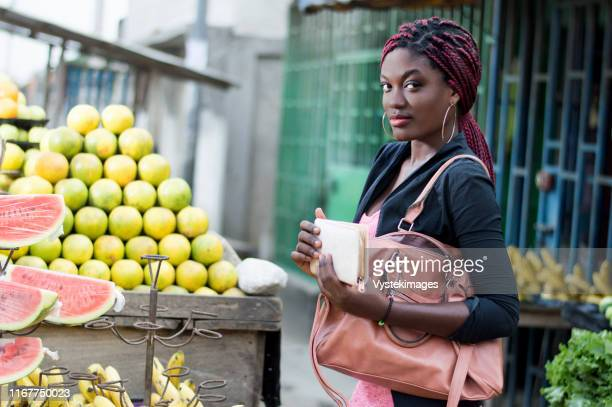 young woman in front of a fruit shelf with her  wallet in her  hands. - áfrica del oeste fotografías e imágenes de stock