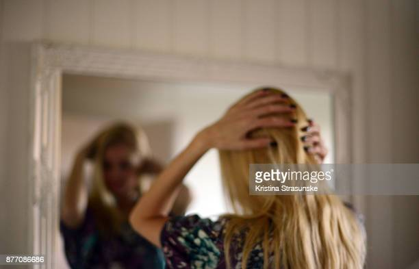 young woman in front of a mirror holding her head in her hands - woman in mirror stock photos and pictures