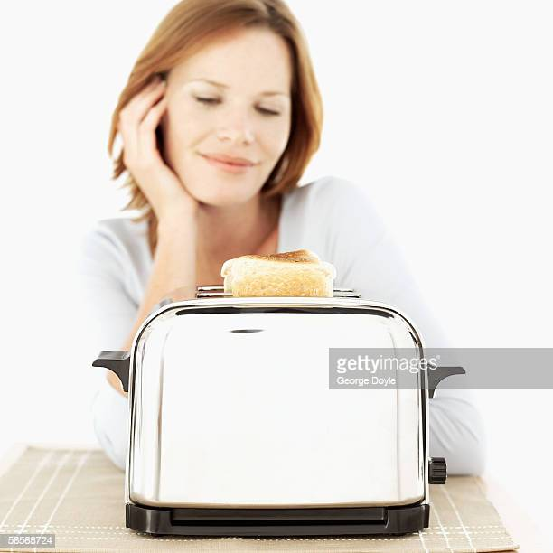 young woman in front of an electric bread toaster