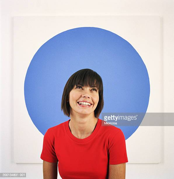 young woman in front of blue circle, looking up, smiling - microzoa stock pictures, royalty-free photos & images