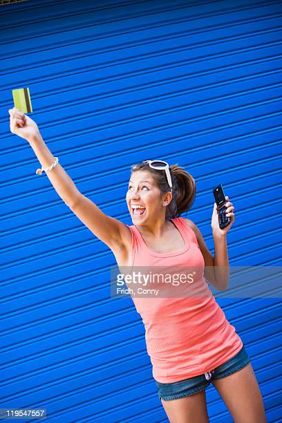 Young woman in front of blue wall, holding credit card and cell phone