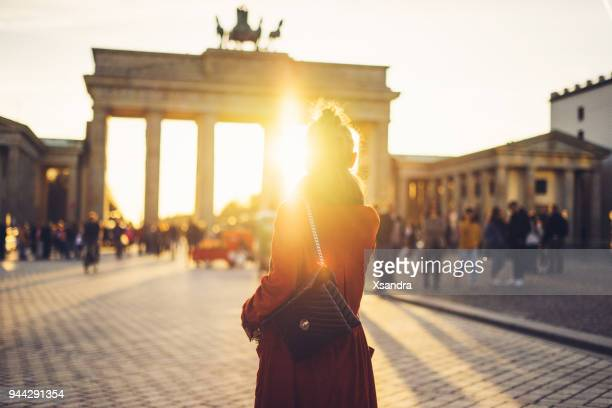 young woman in front of brandenburger tor in berlin, germany - berlin stock pictures, royalty-free photos & images