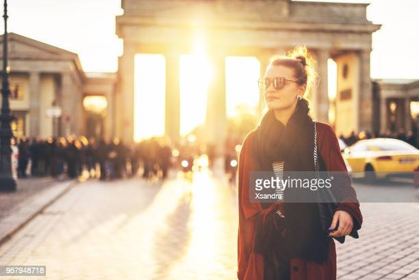 young woman in front of brandenburger tor in berlin, germany - central berlin stock photos and pictures
