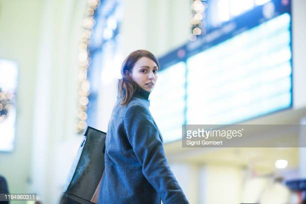young woman in front of digital board in train terminal - sigrid gombert stock-fotos und bilder