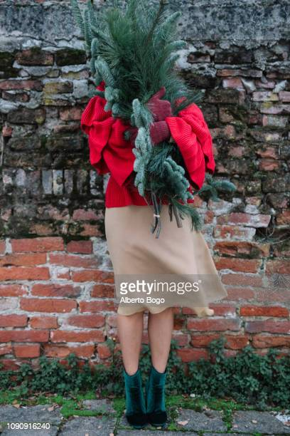 young woman in front of old brick wall holding christmas tree - sapin de noel humour photos et images de collection
