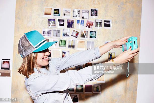 Young woman in front of photo wall taking instant selfie