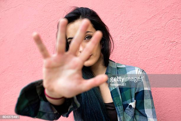 Young woman in front of pink wall looking through her fingers