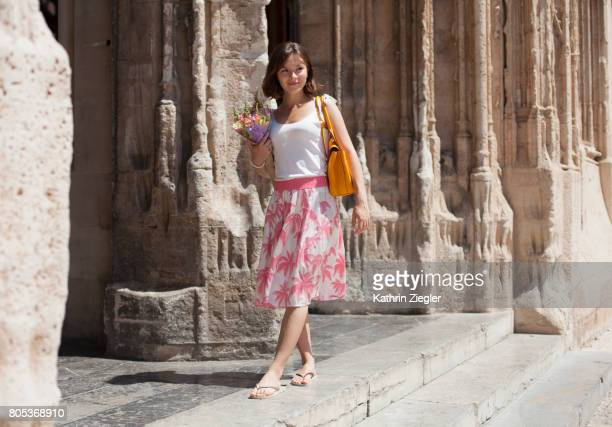 """Young woman in front of Spanish Gothic building """"La Lonja"""" in Palma de Mallorca"""