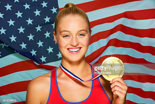 young woman in front of usa flag with gold medal - médaille d'or photos et images de collection