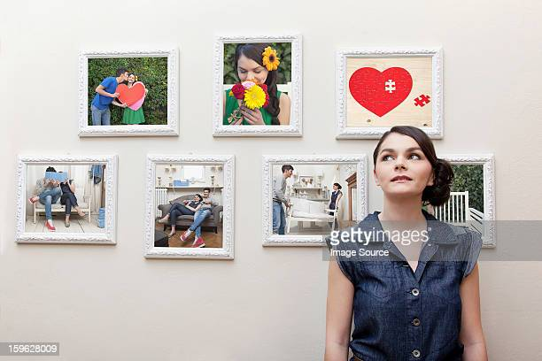 Young woman in front of wall of photographs
