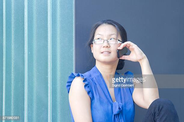 young woman in front of wall talking on smartphone - sigrid gombert stock pictures, royalty-free photos & images