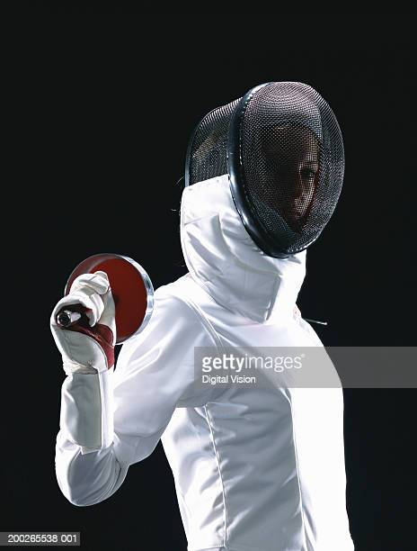 Young woman in full fencing outfit, holding foil behind back, portrait