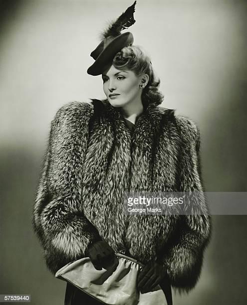 young woman in ファーコートとファッショナブルな帽子のスタジオ(b &w - 毛皮のコート ストックフォトと画像
