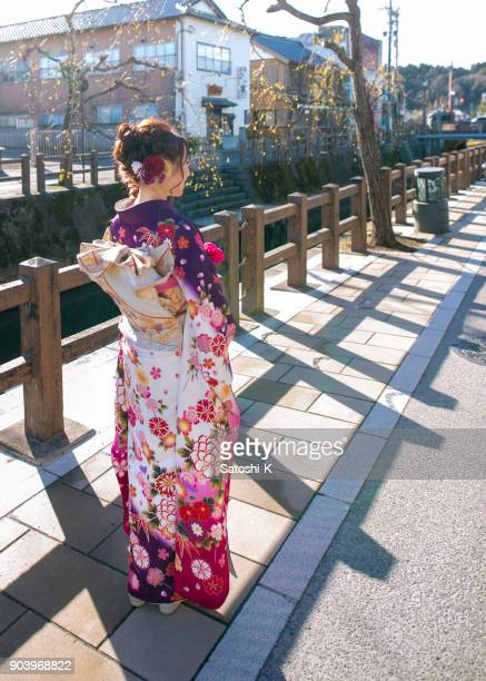 young woman in furisode kimono in traditional japanese town - seijin no hi stock pictures, royalty-free photos & images