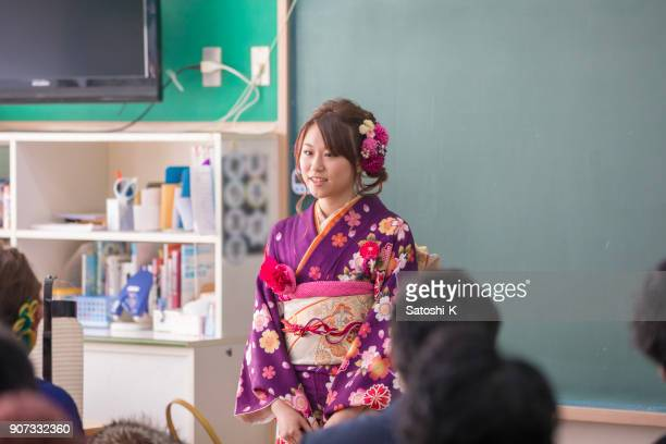 young woman in furisode kimono making speech in classroom - seijin no hi stock pictures, royalty-free photos & images