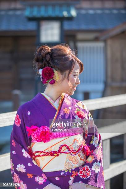 young woman in furisode kimono standing in traditional japanese town - seijin no hi stock pictures, royalty-free photos & images