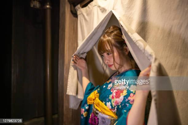 夜に日本の伝統的な「旅館」ホテルの「千蓮」の入り口を歩く「ふりし」着物の若い女性 - のれん ストックフォトと画像