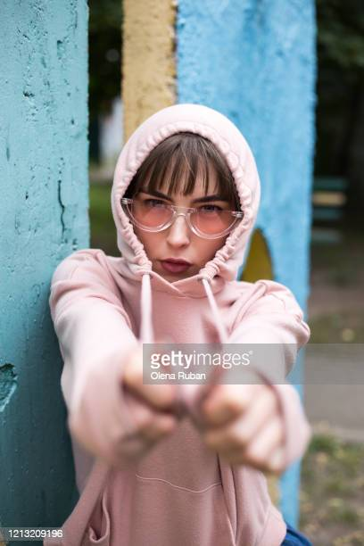 young woman in glasses and pink sweatshirt - reaching stock pictures, royalty-free photos & images