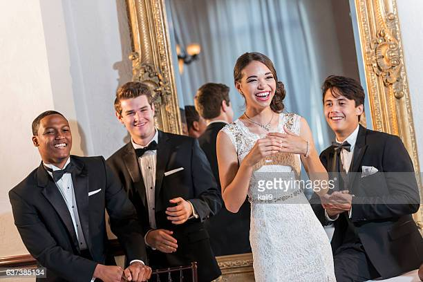 young woman in gown with three men in tuxedos - adulation stock pictures, royalty-free photos & images