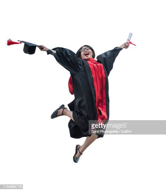 young woman in graduation gown jumping against white background - graduation background stock pictures, royalty-free photos & images