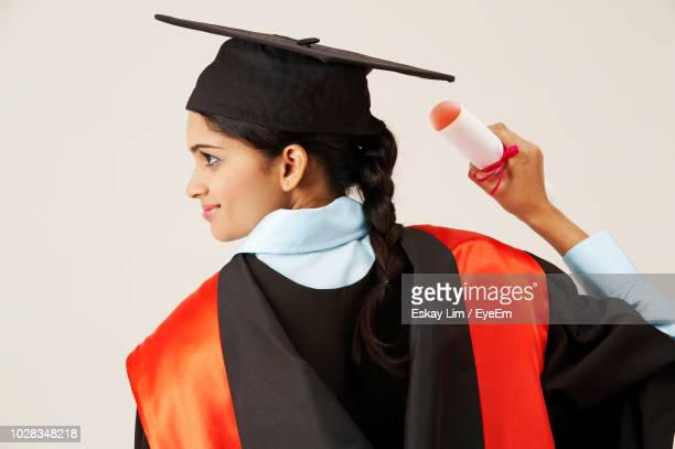 young woman in graduation gown standing against white background - graduation background stock pictures, royalty-free photos & images