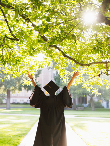 Young woman in graduation gown with raised arms outdoors, rear view - gettyimageskorea