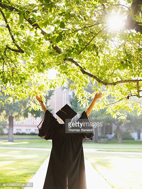 young woman in graduation gown with raised arms outdoors, rear view - graduation gown stock pictures, royalty-free photos & images